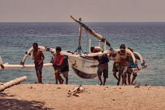 Fishermen carry fishing boat Stock Photography