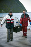 Fishermen carrying fish box. Two fishermen carrying box of freshly caught fish on wooden pier, Norwegian fjord in background Royalty Free Stock Photos