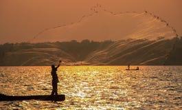 Fisherman throws a net in Lake Victoria. Uganda. Fishermen cast a net in Lake Victoria at a bright sunset. Uganda royalty free stock image