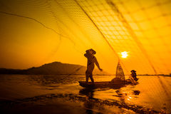 Fishermen casting net from boat at sunrise. Fishermen in small boat on river casting net at sunrise royalty free stock images