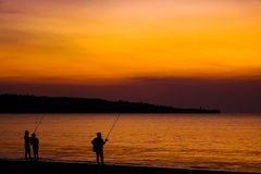Fishermen on the beach on the island of Bali at sunset. royalty free stock images