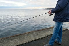 Fishermen catch fish on the pier. Of the Baltic sea Stock Photos