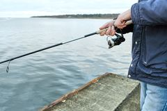 Fishermen catch fish on the pier. Of the Baltic sea Stock Photo