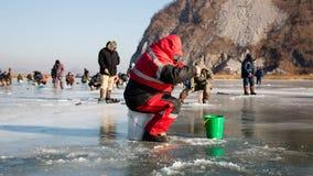 Fishermen catch smelt in winter, Russia Stock Photo