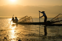 Fishermen catches fish for food in sunrise in Inle lake Stock Images