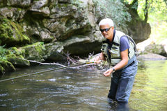 Fishermen catching trouts in the river Stock Photos
