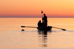 Fishermen checking fishing net in sea on sunrise. Orange sky, calm sea and fishing boat Royalty Free Stock Photos