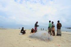 Fishermen clean fish net at seashore Stock Images