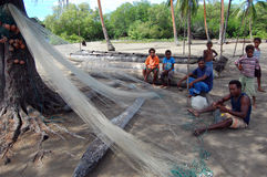 Fishermen cleaning net Papua New Guinea village Stock Image