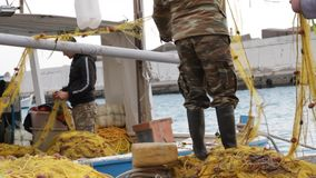 Fishermen cleaning nets on a boat stock video