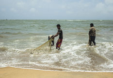 Fishermen cleaning nets Stock Images