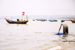 Fishermen with colorful fishing boats on February 7, 2012 in Mui Ne, Vietnam. Royalty Free Stock Images