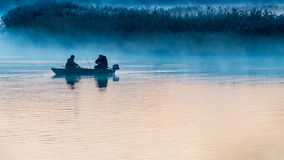 Fishermen at dawn on a river Stock Photography