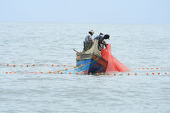Fishermen do fishing by using boat and fishing net Royalty Free Stock Image