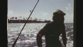 Fishermen driving a motor boat along the coastline. Republic Of Trinidad, Tobago, April 1976. Two shot sequence of three local fishermen driving a small fishing stock video