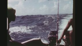 Fishermen Driving With Small Boat In The Open Sea. REPUBLIC OF TRINIDAD, TOBAGO, APRIL 1976. Two Shot Sequence Of Two Native Fishermen Driving A Small Boat In stock video footage
