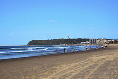 Fishermen on Durban's Addington Beach with Bluff in Background Royalty Free Stock Images