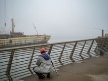 Fishermen examining catch on industrial pier on foggy day stock photography
