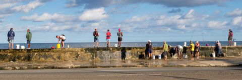 Fishermen at the famous Malecon seawall in Havana. HAVANA,CUBA - NOVEMBER 25,2017 : Fishermen at the famous Malecon seawall in Havana Stock Photo