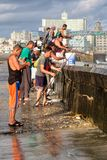 Fishermen at the famous Malecon seawall in Havana. HAVANA,CUBA - NOVEMBER 25,2017 : Fishermen at the famous Malecon seawall in Havana with a view of the city Stock Image
