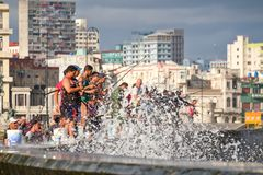 Fishermen at the famous Malecon seawall in Havana. HAVANA,CUBA - NOVEMBER 25,2017 : Fishermen at the famous Malecon seawall in Havana with a view of the city Royalty Free Stock Photography