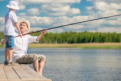 Fishermen father and son on the pier fish. In the lake Royalty Free Stock Photos
