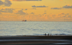 Fishermen, ferry and turbines. Three distant fishermen, on the shore at sunset. In the background, the largest offshore windfarm in the world, with the English Stock Images