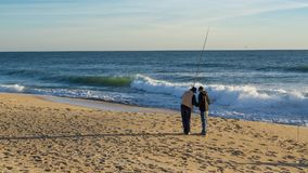 Fishermen fishing on beach at Faro, Algarve, Portugal. stock photography