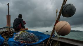 Fishermen in fishing boat at Ko Chang Island Ranong Province Thailand. Rain storm royalty free stock photo