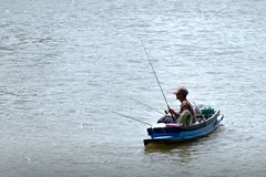 Fishermen are fishing on the boat in the river stock photography