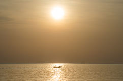 Fishermen fishing on a boat silhouette in morning sunrise light. Royalty Free Stock Images