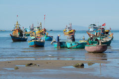 Fishermen and fishing boats are preparing to go to sea for night fishing. The fishing harbour of Mui Ne, Vietnam Stock Photography