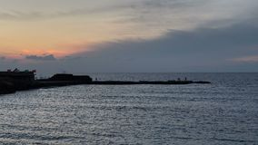 Fishermen fishing at dusk on the breakwater at Crusader`s Port on Caesarea in Israel. stock video