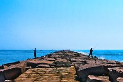 Fishermen fishing on jetty on clear sunny day royalty free stock photo