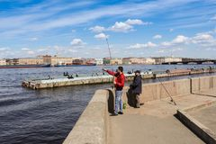 Fishermen are fishing on the Neva River. Architecture of city embankments of rivers and canals Royalty Free Stock Image
