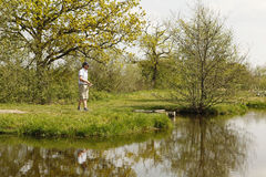 Fishermen at a fishing pond Stock Photos
