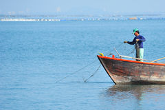Fishermen fishing on the sea. Stock Image