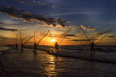 Fishermen fishing in the sea at sunrise Stock Photos