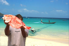 Fishermen, fresh fish & net. Tropical beach. The fisherman is proudly demonstrating big red snapper.  The sea water is dropping down from the fish. Others Stock Photography