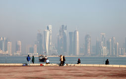 Fishermen in front of Doha skyline Stock Photo