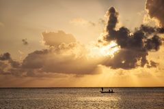 Fishermen going on ocean on traditional fishing boat in Zanzibar. With storm clouds at sunrise Stock Images