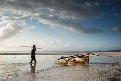 Fishermen going on ocean on traditional fishing boat in Zanzibar. With storm clouds at sunrise stock photo