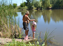 Fishermen. Grandfather with granddaughter fishing on the lake in the summer Stock Photo