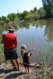 Fishermen. Grandfather with granddaughter fishing on the lake in the summer Royalty Free Stock Photos