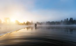 Fishermen holding fishing rod, standing in river stock image