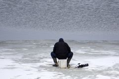 The fishermen on the ice fishing on the river opened . royalty free stock photo