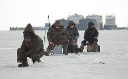 Fishermen on ice in wintertime Stock Images