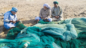 Fishermen In Oman Preparing Nets Royalty Free Stock Image