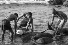 Fishermen from Indonesia,Lamalera. Men from the village Lamalera stow their fishing nets in which a family of dolphins.The village of Lamalera on the Indonesian royalty free stock photo