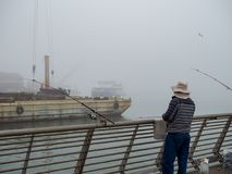Fishermen on industrial pier on foggy day royalty free stock image